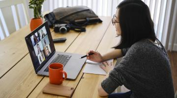 A woman working at home participating in a online web meeting.
