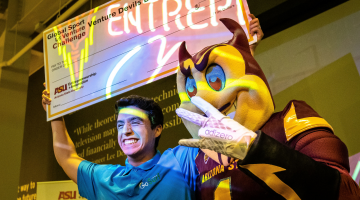 Founder of GoSurf, Aleksei Stojanovic, pictured next to Sparky the ASU mascot holding an oversized check above his head, smiling.