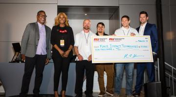 A group of sport entrepreneurs stand on stage, one holding an oversized check with their funding amount displayed.