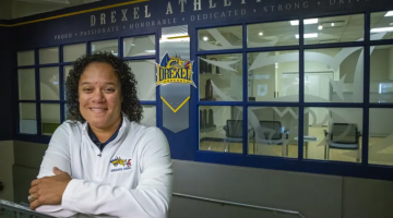 Maisha Kelly resting arms over metal rail, in front of windows with signage above stating: Drexel Athletics, proud, passionate, honorable, dedicated, strong, driven.