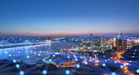 """A lit modern city skyline as either dusk or dawn, with an overlay of blue """"network"""" graphics."""
