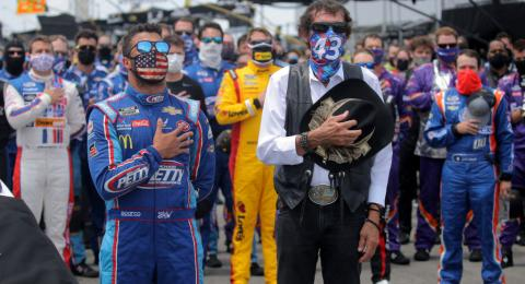 Bubba Wallace, driver of the #43 Victory Junction Chevrolet, and team owner, and NASCAR Hall of Famer Richard Petty stand for the national anthem prior to the NASCAR Cup Series GEICO 500 at Talladega Superspeedway on June 22, 2020 in Talladega, Alabama.