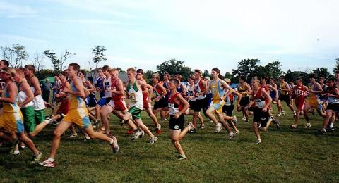 Luke Brenneman, center in red and black, turned to cross country when his delayed puberty made contact sports too difficult. He is seen here running amongst many other teens.