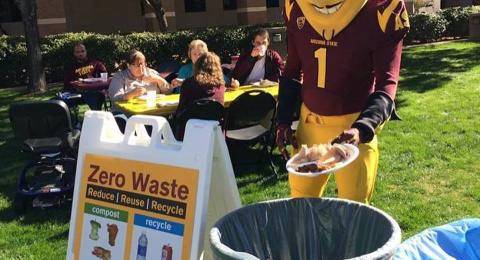 Sparky the ASU mascot stands in front of different waste bins with a plate.