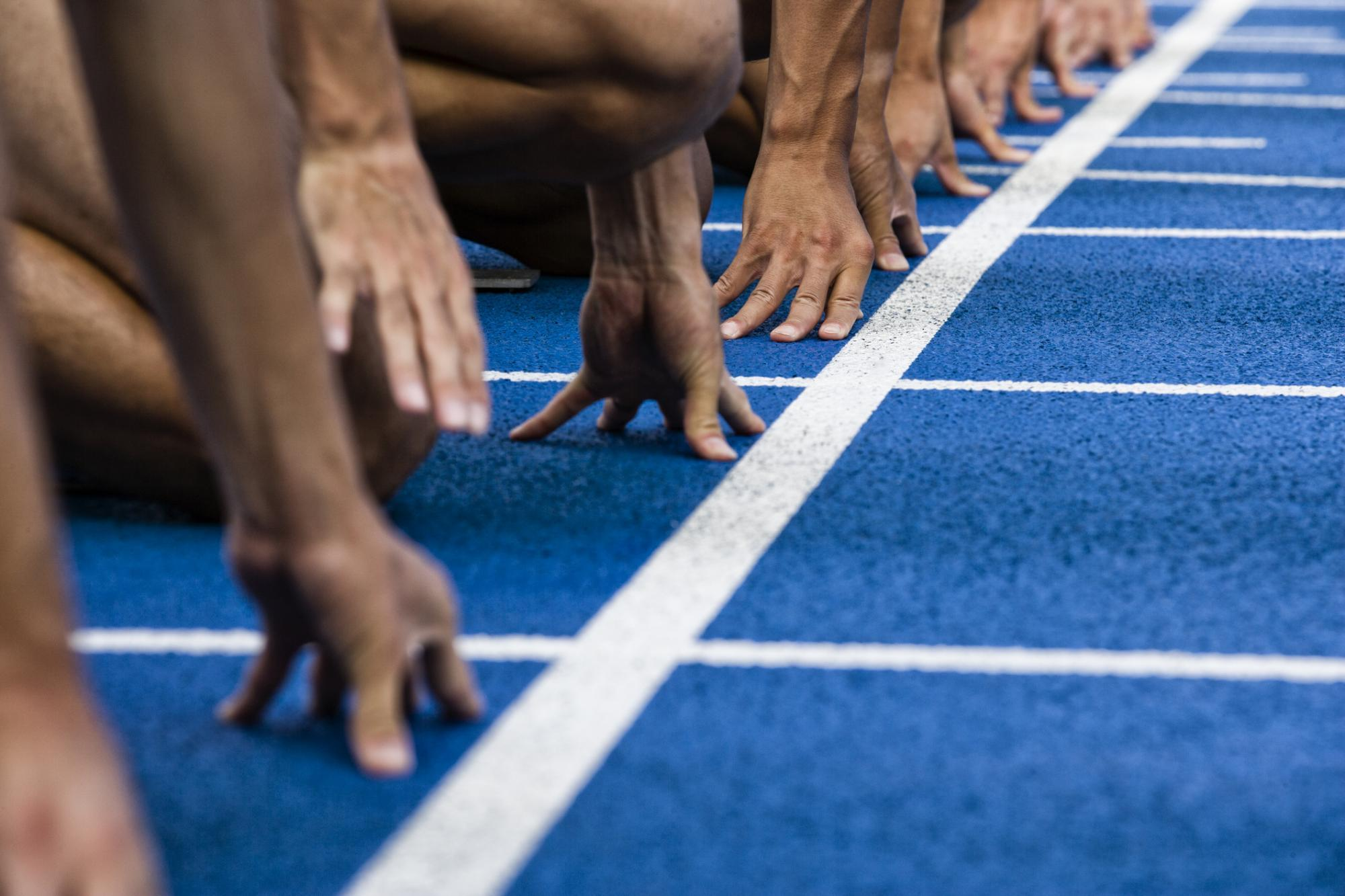 The hands of runners in start position at the start line of a race on a track.