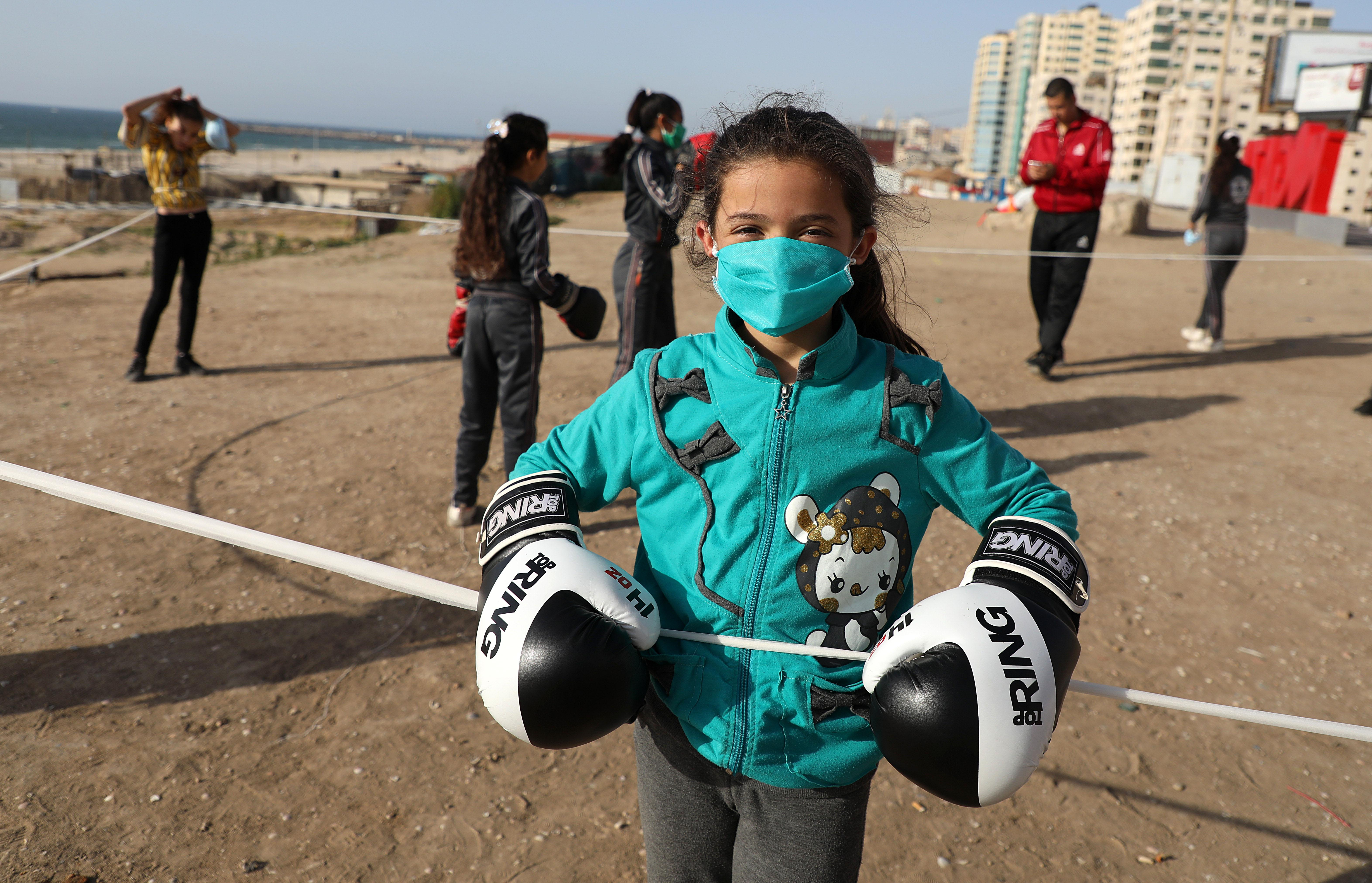 Palestinian girls clad in masks due to the COVID-19 coronavirus pandemic take part in an open-air boxing training near the beach in Gaza City on May 12, 2020. (Photo by Majdi Fathi/NurPhoto via Getty Images)