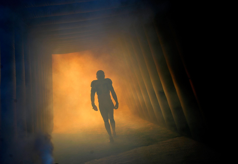 Football player running through tunnel